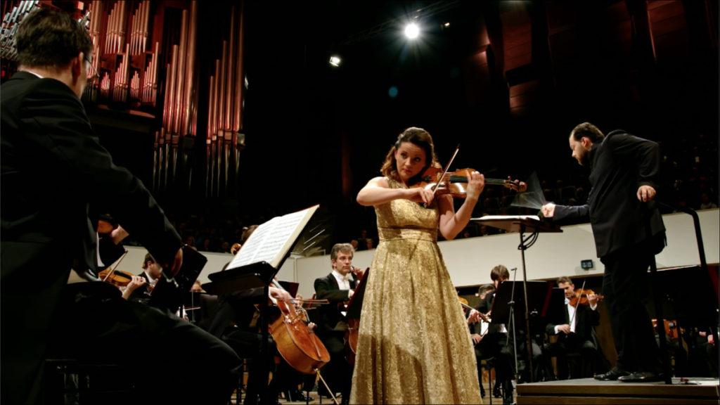 ショスタコーヴィチのヴァイオリン協奏曲第1番を演奏するバイバ・スクリデとアンドリス・ネルソンス指揮ライプツィヒ・ゲヴァントハウス管弦楽団(2019年5月)。(c) Accentus